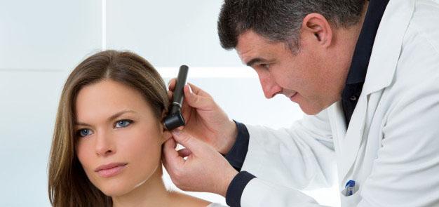 Un médecin examine l'oreille avec l'otoscope
